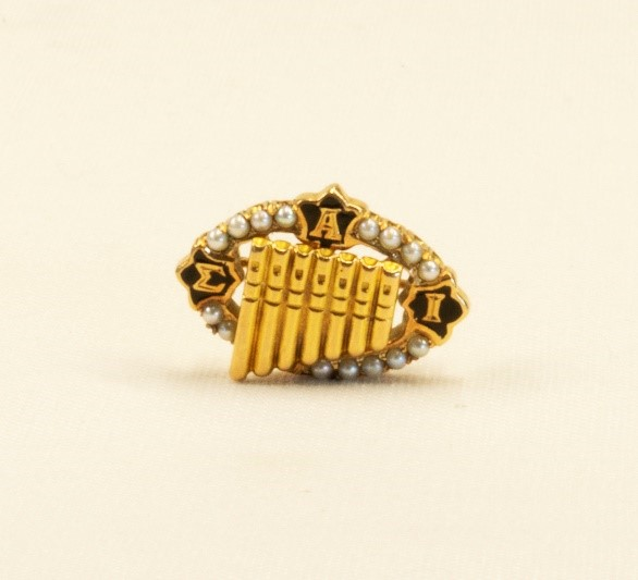 A lapel pin in the shape of a pan flute from the Sigma Alpha Iota music fraternity, (ca. 1930).